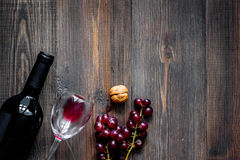 Serve wine. Bottle, glass, nuts and grape on wooden table background top view copyspace Royalty Free Stock Images