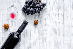 Serve wine. Bottle, glass, nuts and grape on wooden table background top view copyspace Royalty Free Stock Photos