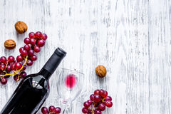 Serve wine. Bottle, glass, nuts and grape on wooden table background top view copyspace Stock Image