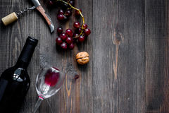 Serve wine. Bottle, glass, nuts and grape on wooden table background top view copyspace Stock Photo