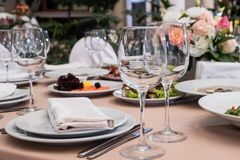 Served for banquet restaurant table with dishes, snack, cutlery, wine and water glasses, european food, selective focus. Served for banquet restaurant table with royalty free stock photography