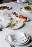 Served for banquet restaurant table with dishes, snack, cutlery, wine and water glasses, european food, selective focus. Served for banquet restaurant table with stock images