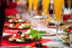 Served for a banquet table. Wine glasses with napkins, glasses and salads royalty free stock photos