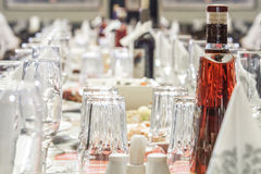 A served banquet table. With glasses, drinks, tableware, snacks and napkins Royalty Free Stock Image