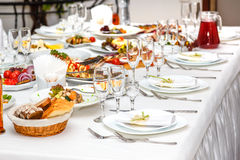 Served banquet table with plates, glasses and dishes Stock Photos