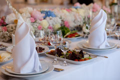 Served for a banquet table. Wine glasses with napkins, glasses and salads. Stock Images