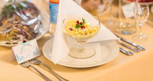 Served for a banquet table. Wine glasses with napkins, plate and salads. Stock Photo
