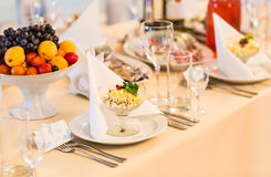 Served for a banquet table. Wine glasses with napkins, plate and salads. Stock Photography
