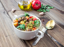 Served beef meat stewed with vegetables in ceramic pot with ingredients on wooden background Stock Image