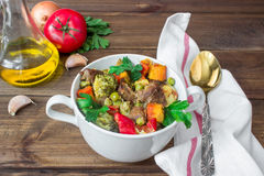 Served beef meat stewed with vegetables in ceramic pot with ingredients on wooden background. Served beef meat stewed with potatoes, carrots and spices in Royalty Free Stock Photos