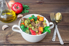 Served beef meat stewed with vegetables in ceramic pot with ingredients on wooden background Stock Photos
