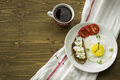 Served breakfast with a Fried egg in form of a clock and coffee. Breakfast: Fried egg in form of a clock, tomato, sandwich and coffee Royalty Free Stock Images