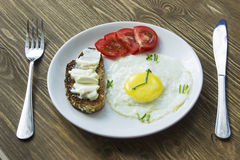 Served breakfast with a Fried egg in form of a clock. Breakfast: Fried egg in form of a clock, tomato and sandwich with fork and knife Stock Image