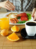 Served breakfast on a table. A woman is having breakfast in the background Stock Images