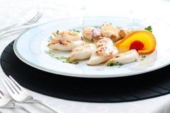 Served calamari. Calamari on white plate in restaurant Stock Photo