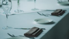 Served dining table at expensive restaurant, white cloth, plates, brown napkins stock video footage