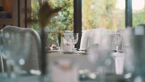 Served dining tables at expensive restaurant, trees behind windows stock footage