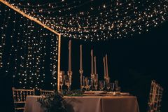 Served dinner table with candles and garlands. royalty free stock image
