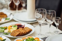Catering table set service with silverware and glass stemware at stock photo