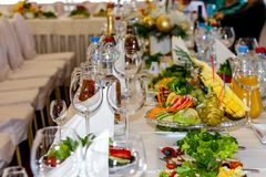 Served dishes to the table for holiday. Cutlery and food on white tablecloths in the restaurant. Design a festive Banquet. stock photography