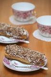 Served eclairs. For a couple on a wooden table with pink cups Stock Images