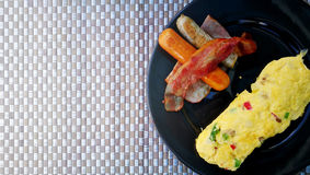 Served healthy protein breakfast with sausage and omelet on black plate. Stock Photos