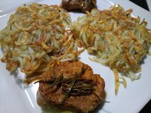 Two piles of crispy stringy potatoes and pork fillet Stock Image