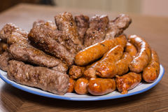 Served kebabs and sausages from bbq on the plate Royalty Free Stock Image