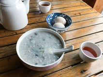 Served local chinese breakfast in rustic eatery. Travel to China - served local chinese breakfast from eggs and congree rice porridge with century eggs (pidan) Stock Photos