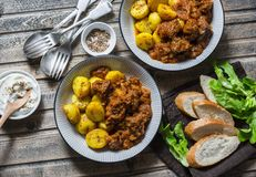 Served lunch table - irish beef stew with bombay turmeric potatoes. Delicious seasonal food on a wooden background, top view. royalty free stock image