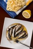Served marinated sardines in the oil with lemon and corn bread Stock Photo