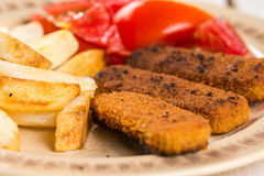 Served meal on the table, fried fish meat sticks with potatoes and tomato salad Royalty Free Stock Images