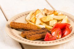 Served meal on the table, fried fish meat sticks with potatoes and tomato salad stock photo