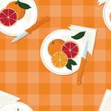 Served oranges. On checked background Royalty Free Stock Image