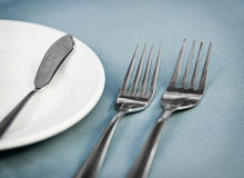 Served restaurant table with forks, white plate and knife Royalty Free Stock Photo