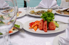 Served restaurant table. Salad with vegetable in restaurant. Salad with tomato, pepper and cucumber in white plate close up. Served restaurant table. Wedding Royalty Free Stock Images