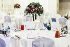 Served round wedding table with red and green bouquet in the mid Stock Images