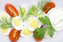 An overhead photo of vegetable salad with mayonnaise, boiled quail egg, dill, fresh tomato and parsley on white porcelain plate. A. A served salad photo from Stock Photos