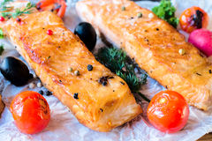 Served salamon fillets. Juicy prepared salmon fillets and grilled tomato,selective focus Stock Photo