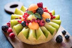 Served slice melons with berry fruits Stock Photos