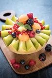 Served slice melons with berry fruits Stock Photo