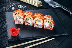 Served sushi rolls on black stone with chopsticks. Close up view on sushi on dark background. stock photo
