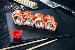 Served sushi rolls on black stone with chopsticks. Close up view on sushi on dark background. stock images