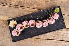 Served sushi rolls with garnish, top view. Sushi with rose flowers garnish and caviar Stock Photo