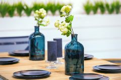 Served table with black plates, glass vases with flowers. Dinner table decoration royalty free stock photos