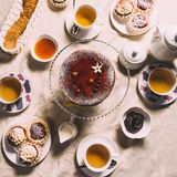 Served table with a cup of tea and chocolate cakes stock photography