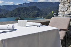 Served table with empty plate, lake Bled, island and Alps Stock Photos