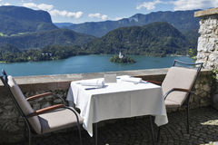 Served table with emty plate, lake Bled, island and Alps Stock Photo