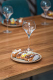 Served table for food and vine tasting. Eclairs with different ganache and icing with different toppings Royalty Free Stock Photos