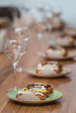 Served table for food and vine tasting. Eclairs with different ganache and icing with different toppings Stock Photos